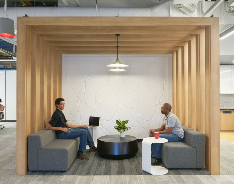 Two men sit in a lounge space divided off in a cubic shape by wooden Fortina panels. Within the cubic space is a white branch patterned Iconic Panel wall.