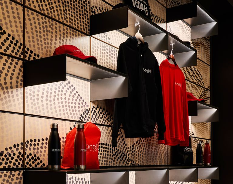 Close-up shot of dotted Infused Veneer panels working with black System 1224 shelves showcasing Planet 13 merchandise.