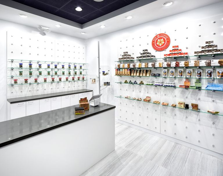 """View of the interior of a white coffee shop. A white counter with a black top is placed in front of two white walls both utilizing the puck system. Glass shelves are held up against each wall displaying a variety of different snacks. Over the shelves, an orange circle with the logo for """"Pot-O-Coffee. Cannabis Coffee"""" is hung."""