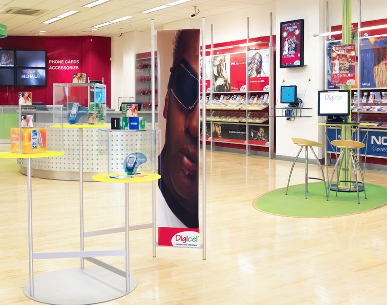 Interior of a colorful phone store. Yellow display stands showcase various phones. Phones are also on display along the walls.