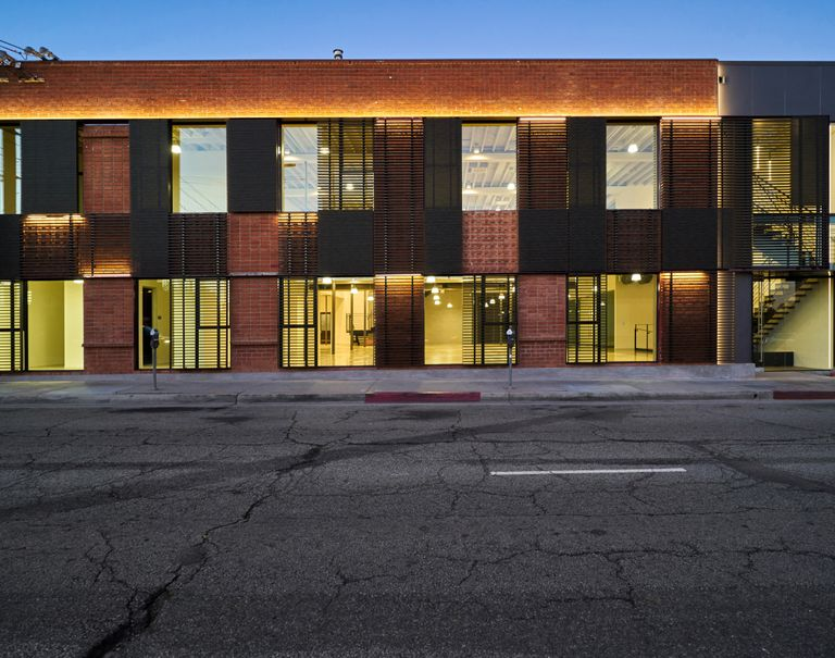 A side view of a lit brick building with glass windows.