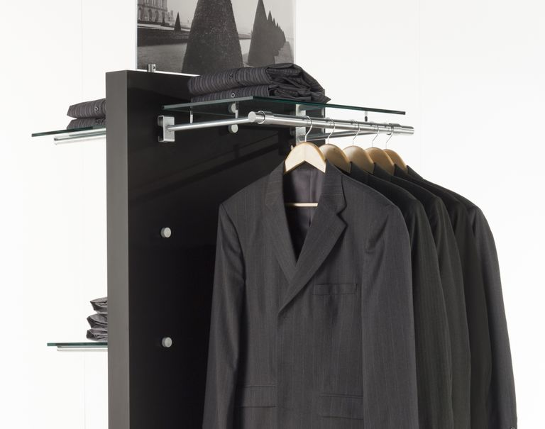 Various black clothing articles are on display against a black standing panel with metal Puck fixtures attached to it. The fixtures hold up metal bars and glass shelves for the clothes to be displayed on.