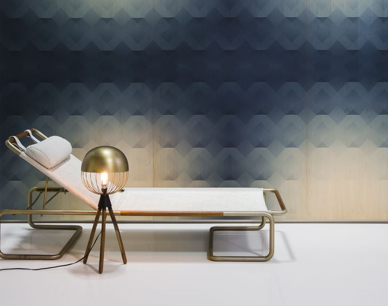 A white lounge chair is placed in front of a navy blue and circular tan patterned Veneer Panel wall.