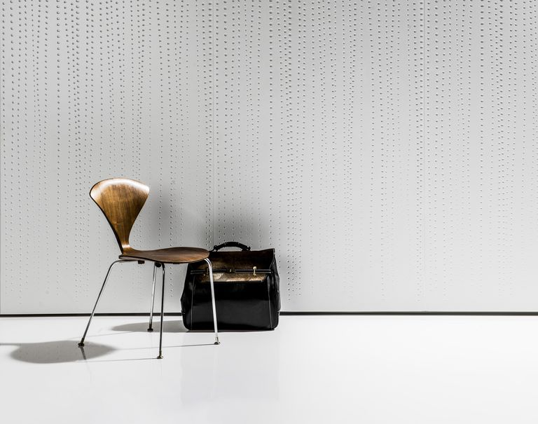 A wooden chair with a black suitcase are propped in front of a white wall decorated in dotted Iconic Panel.