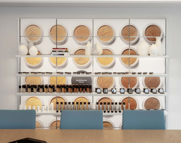 View of a wall decorated with lit up panels with an image of different foundation powders. The panels are equipped with white System 1224 shelves showcasing miscellaneous items including makeup products, books, and vases.