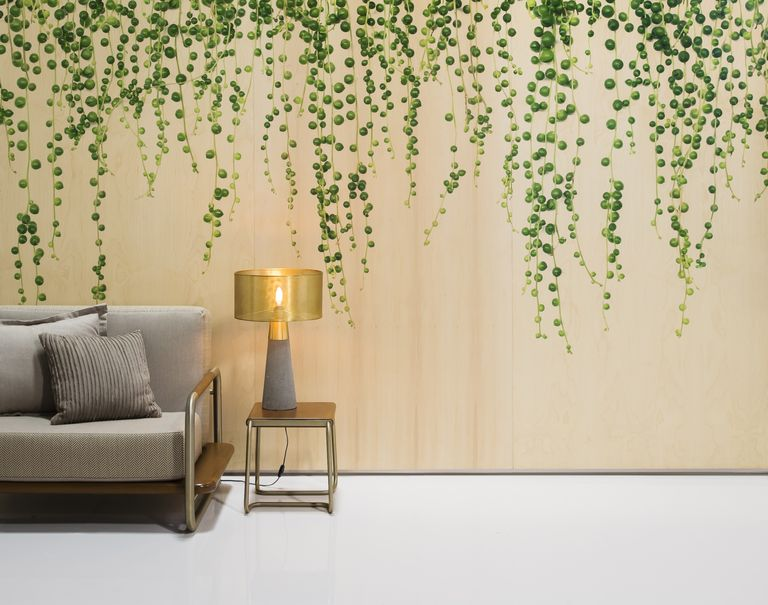 A gray couch and small wooden stand with lamp stand in the corner in front of a large wall decorated with Ivy plant patterned wooden Infused Veneer.