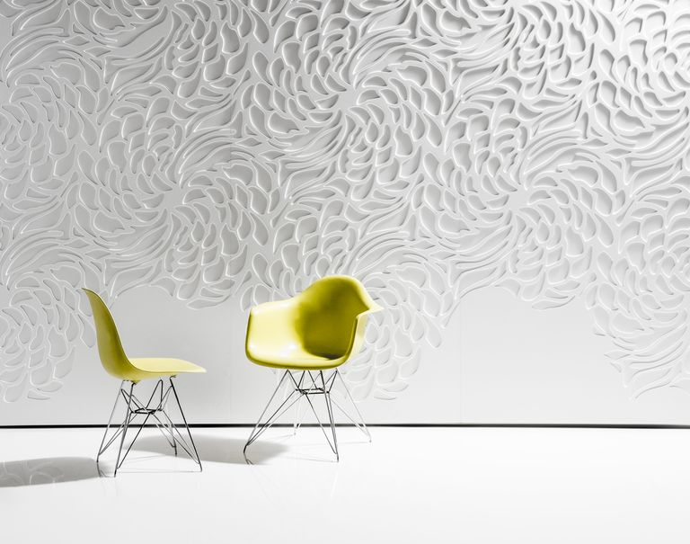 A white wall is decorated with Iconic Panels in floral patterns and two lime colored chairs sit in front of it.