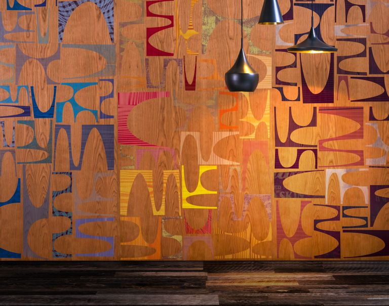 Several black lamps hang over in front of a colorful patterned Infused Veneer paneled wall.