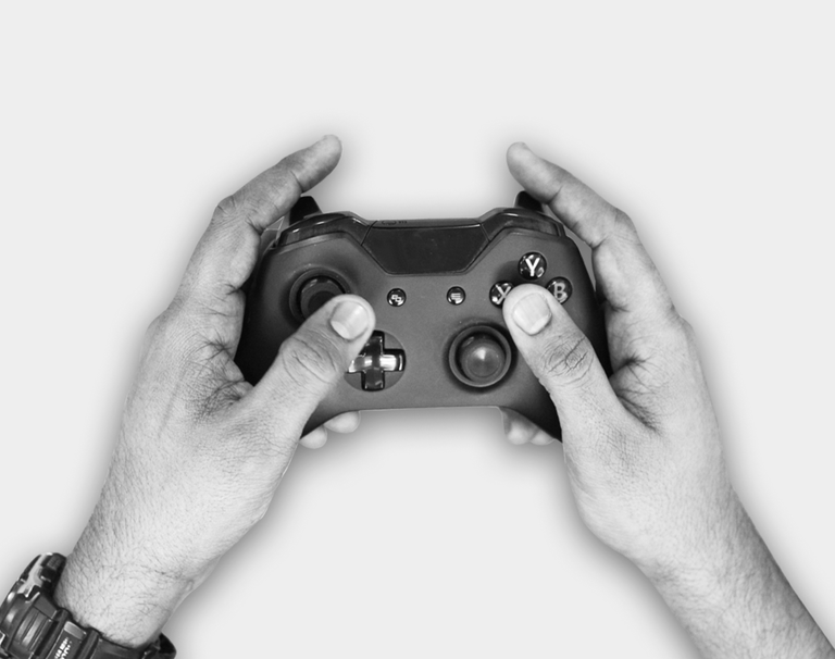 A hand holding and XBox controller