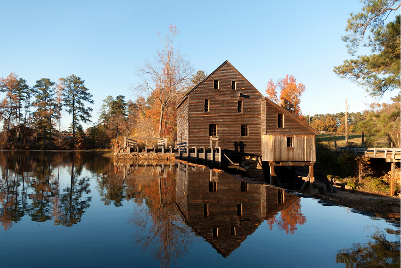 The old gristmill at the Historic Yates Mill Country Park.casts a serene reflection onto the cool pond below.