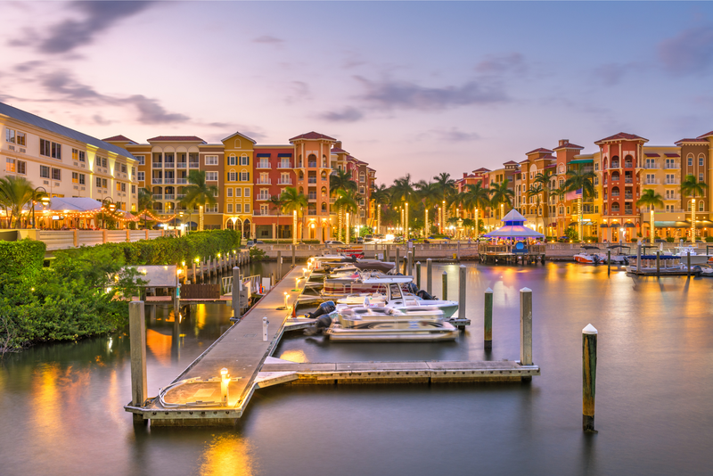 Naples, Florida, USA town skyline on the water at dusk.