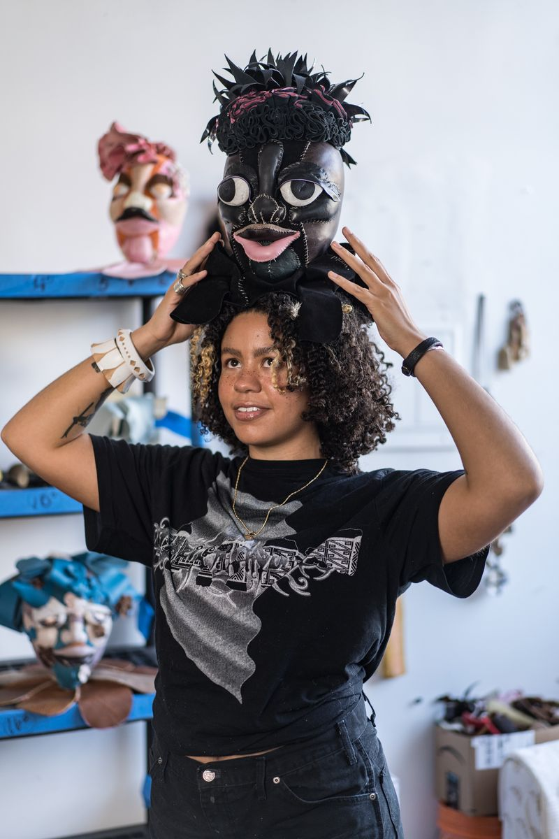 Artist Tau Lewis is holding her sculpture in textile from the series The Church of Mantic Plants