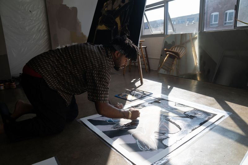 artist viewed from the side whilst leans over and works on his art in his studio
