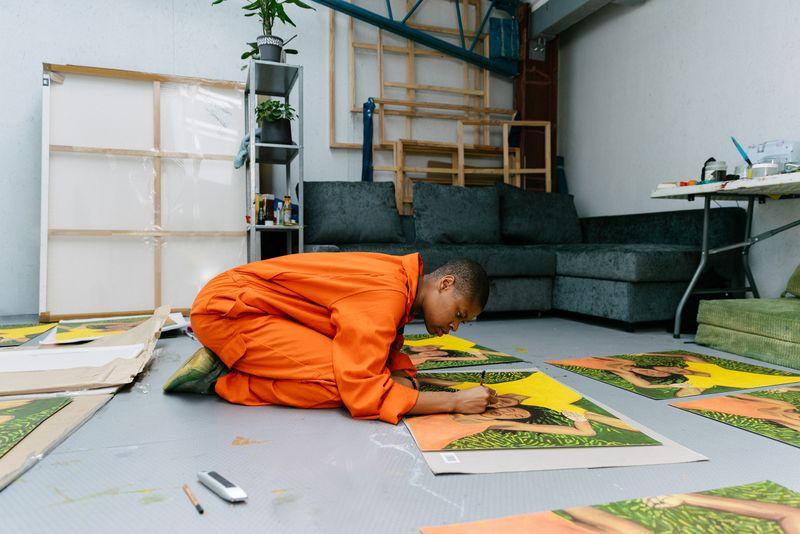 Artist Sola Oluloede hand-finishing her print in her studio