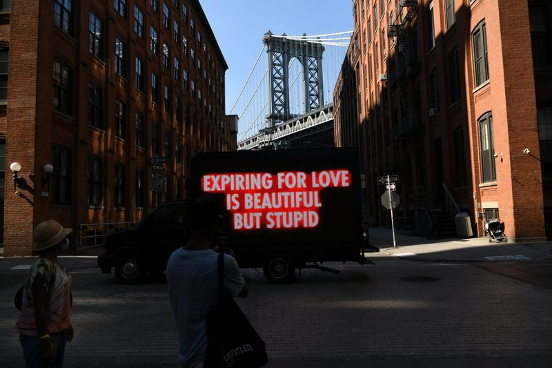 A truck with slogans standing on a street, Jenny Holzer - NYC AIDS Memorial