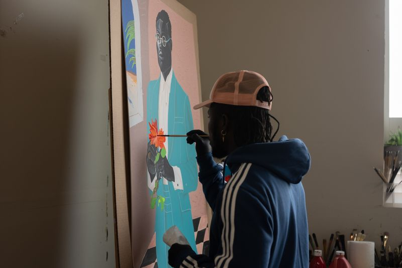 artist Otis Kwame Kye Quaicoe hand holding a paintbrush up to a painting to add detail to an orange flower