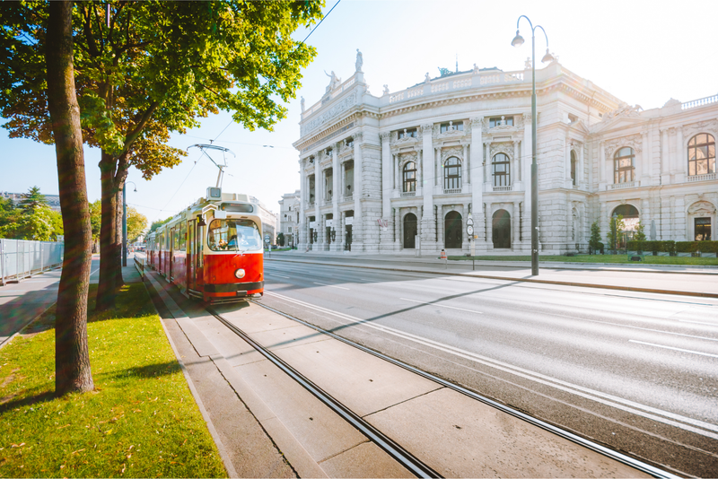 A red tram outside the historic Burgtheater (Imperial Court Theatre) in Vienna, Austria