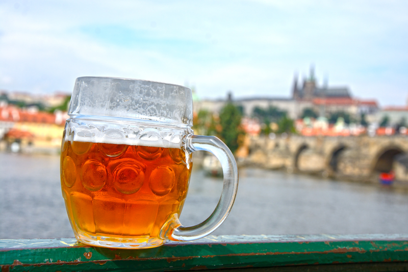 A pint of beer with a view of Prague in the background