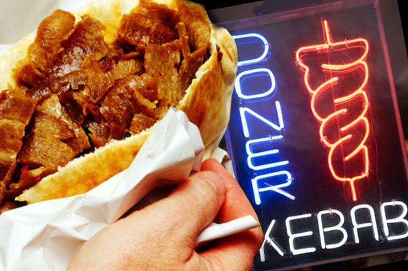 A doner kebab outside a kebab shop at night