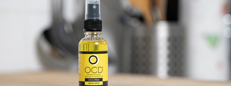 yellow lemon ocd spray bottle full of yellow liquid sat on top of a wodden chopping board in a kitchen