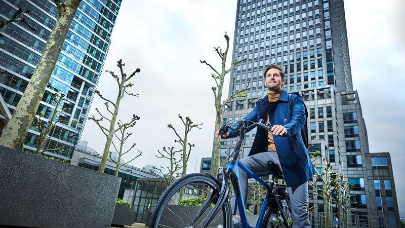 Man voor kantoorgebouw op a-Shine M8b e-bike