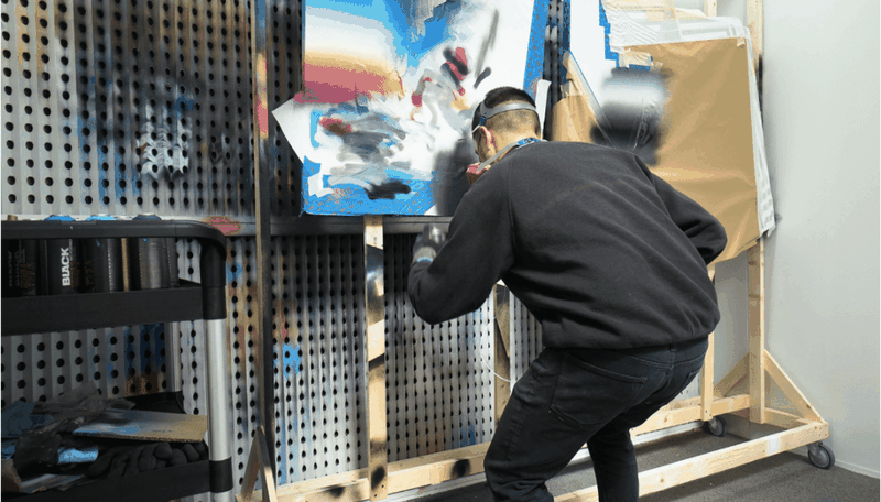man with mask on as he adds paint to a colourful canvas hung up in front of him