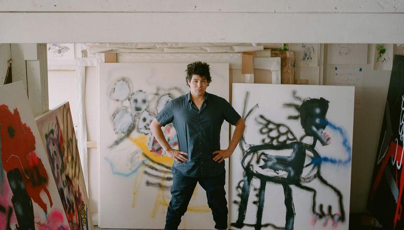 Robert Nava standing in his studio with his hands on his hips