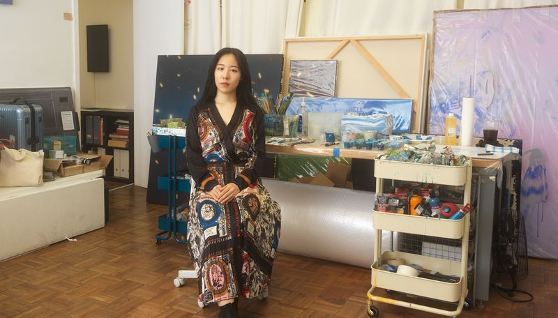 Sarah Lee sat in her studio in front of several large painted canvases