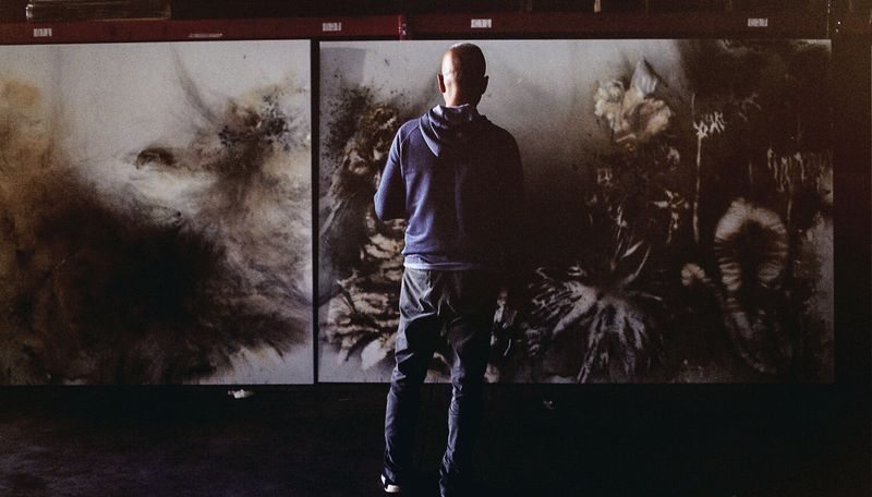 artist with his back turned to camera in a dark room gazing towards the large painting that stands before him