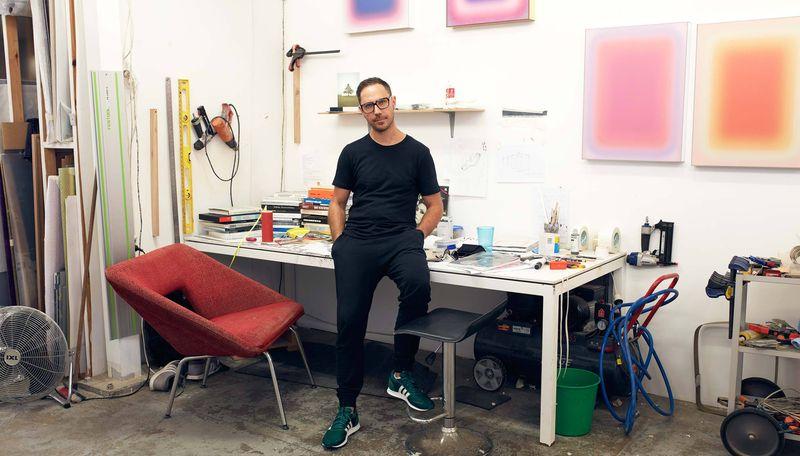 artist Jonny Niesche leans on a desk in his studio