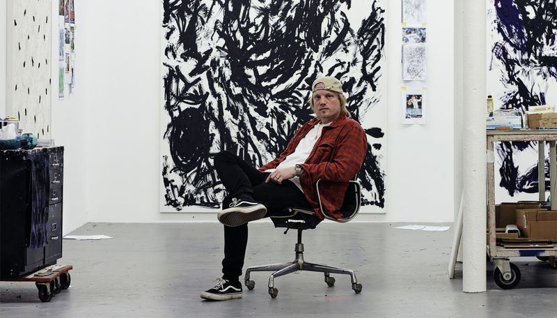 Chris Succo sat on a chair with one leg crossed over the other in his studio