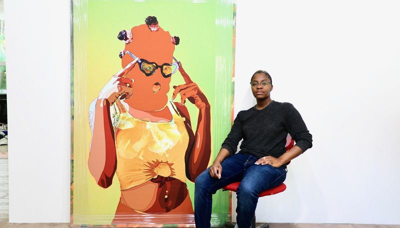 Amani Lewis sat in their studio on a red chair with a large painting behind them