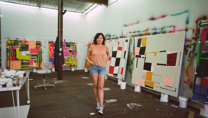 Trudy Benson stood in her studio surrounded by four large paintings
