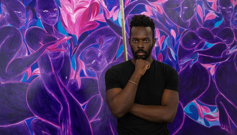 Tunji Adeniyi Jones stood in front of two large purple canvases with his head resting on his fist