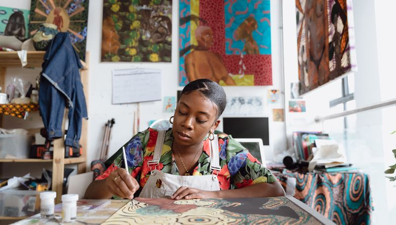 Shannon Bono concentrating on a painting on a table in front of her in her studio