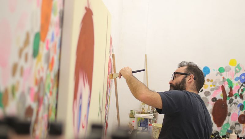 artist holding a paintbrush up to a row of canvases in his studio