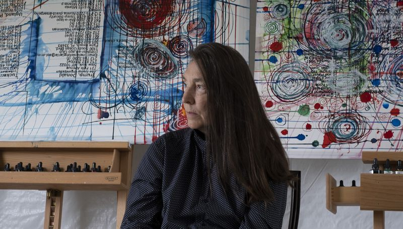 Jenny Holzer sitting in her studio, glancing to the side, with two paintings on easels behind her
