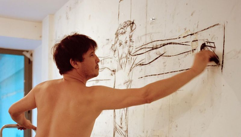 Adel Abdessemed holding onto a small ladder and reaching to draw on a wall