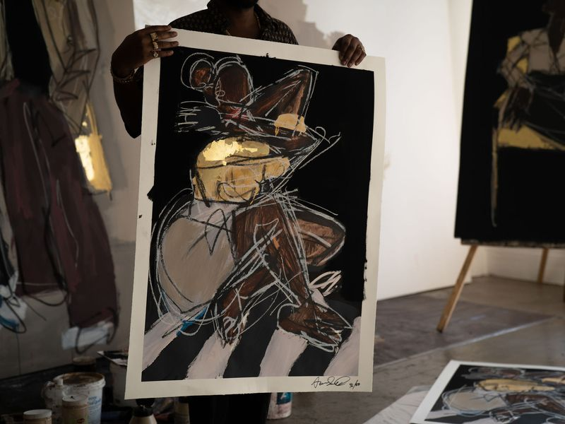 artist holding up his large print in front of his body in his studio