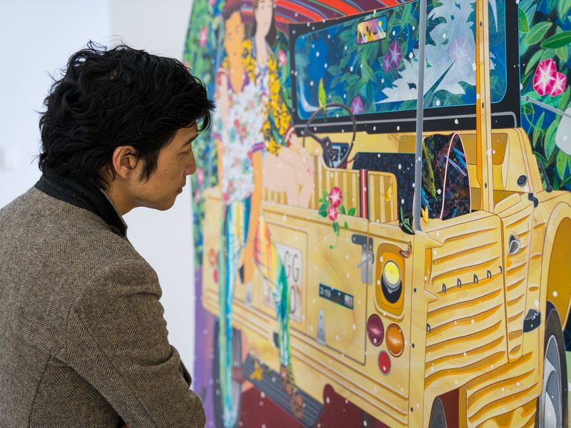 artist standing in front a print with a yellow vehicle and patterned background