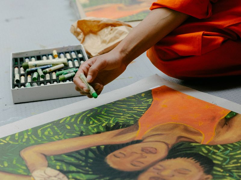 Artist Sola Oluloede hand-finishing her print in her studio - close up