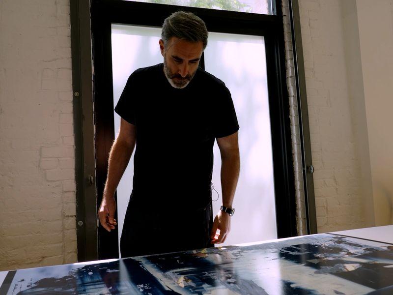 artist Michal Kagan looking at his print Critical Mass