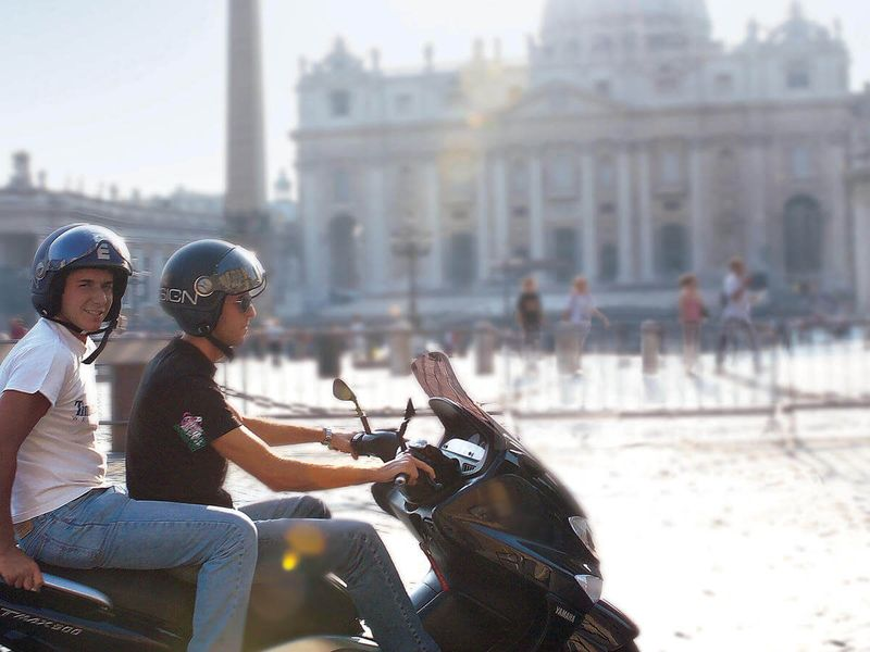 two italian men riding on moped in front of the vatican in vatican city