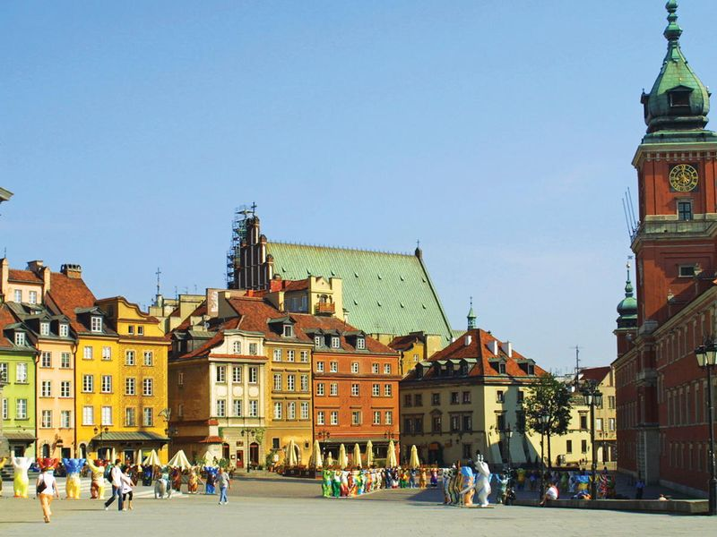 people walking around castle square in warsaw old town in poland