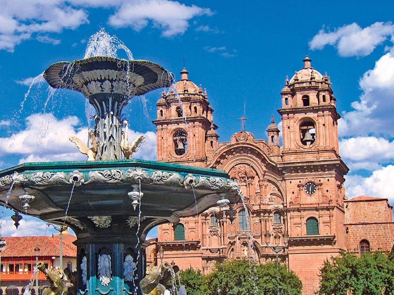 running fountain in front of cathedral and the church of the society of jesus in cusco peru