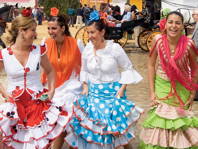 four spanish women dressed in colorful dresses dancing outside in a plaza