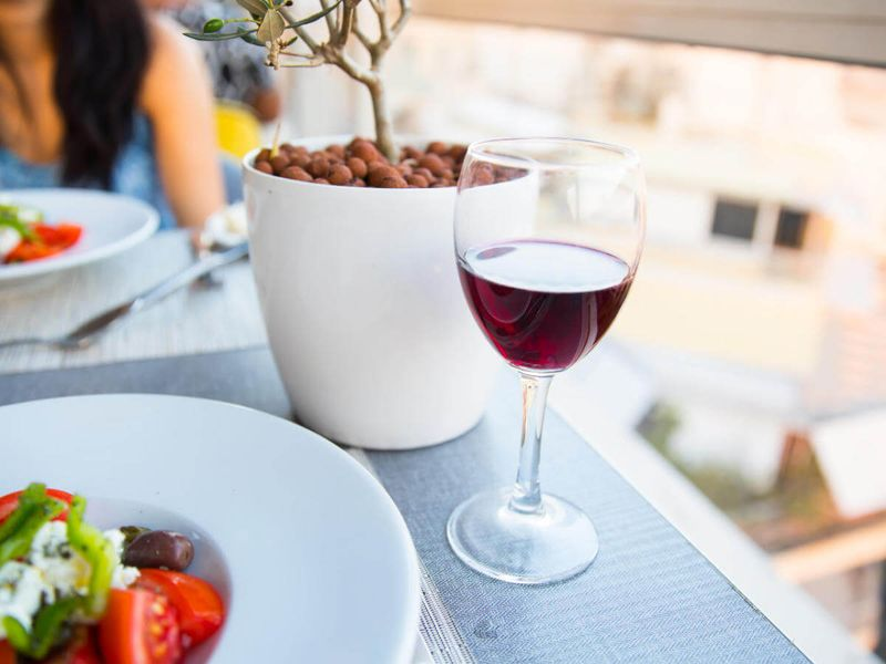 glass of red wine with greek salad