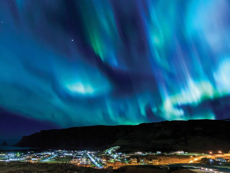 blue and green northern lights floating over city of reykjavik in iceland
