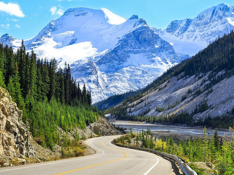 paved road leading to snow capped mountains in jasper national park in canadian rockies
