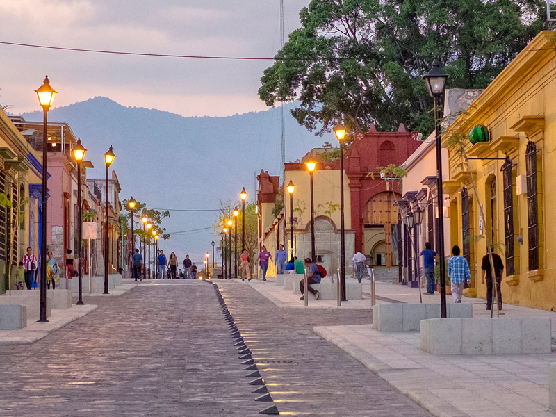 an evening street scene in mexico with yellow pink and red buildings